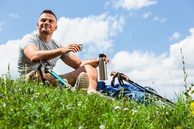 상쾌한 음료를 즐기면서 잔디에 앉아 보철물을 가진 긍정적 인 젊은이