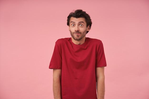 赤いtシャツを着て、手を下に立って、目を大きく開いて見て、額を収縮させ、眉を上げる、流行のヘアカットを持つポジティブな若い男