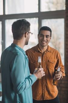 즐거운 대화를 나누면서 맥주를 마시는 긍정적 인 젊은이