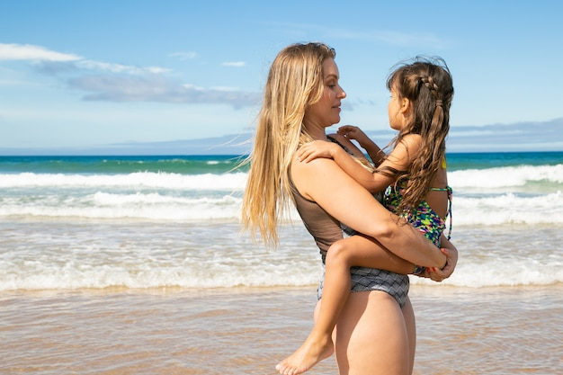 Позитивная молодая мама держит маленькую дочь на руках, неся ребенка, стоя на пляже