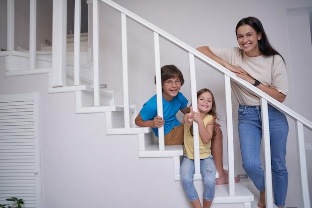 긍정적인 젊은 어머니와 그녀의 두 명의 귀여운 어린 아이들이 카메라를 보고 웃고 있는 동안