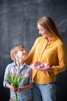 イースターの巣を持ったポジティブな若い母親と、イースター休暇を楽しみながらお互いを見つめるチューリップの花束を持った息子