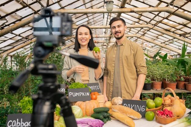 温室でビデオレビューを撮影しながらカメラにリンゴを示すポジティブな若い多民族のカップル