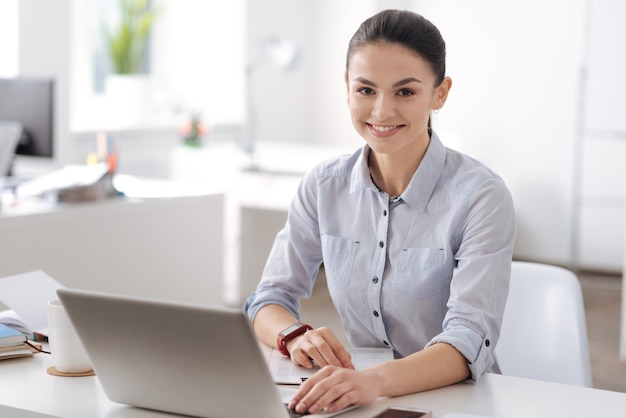 Positive young office worker keeping smile on her face holding hands on computer while sitting at workplace
