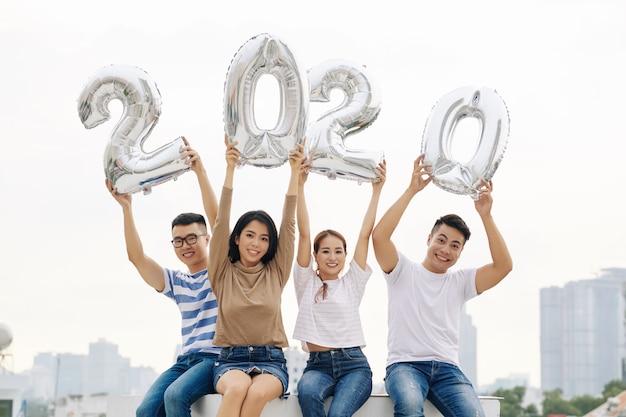 Позитивные молодые люди показывают фольгированные шары