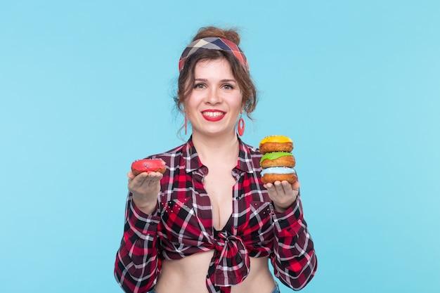 青い背景にポーズをとる4つの色とりどりのドーナツを手に持っているポジティブな若いピンナップガールモデル。デザートやスイーツの料理のコンセプト。広告スペース