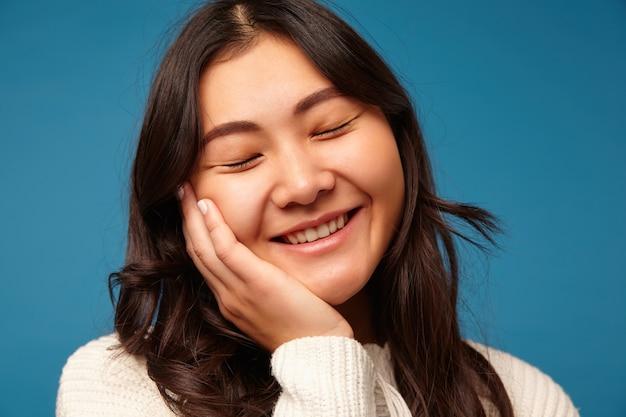 喜んで笑っているポジティブな若い気持ちの良いブルネットの女性