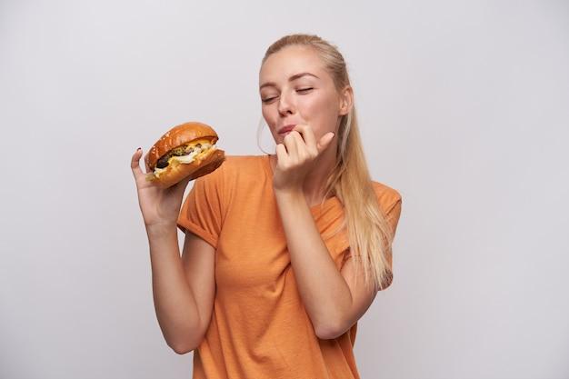 ポニーテールの髪型のポジティブな若いきれいなブロンドの女性は、上げられた手でおいしいチーズバーガーを保持し、白い背景に立って彼女の指をなめる