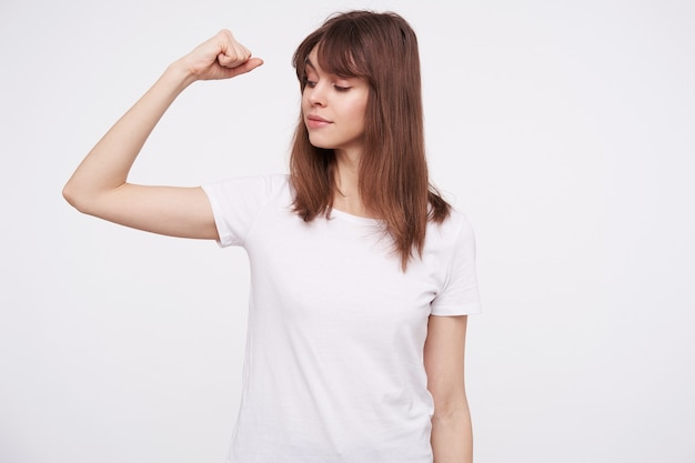Positive young pretty brown haired female with natural makeup raising hand and looking on her biceps, dressed in casual clothes while posing over white wall