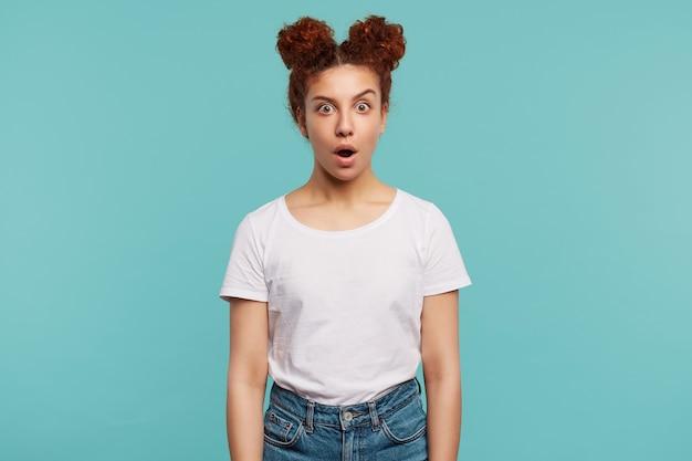 お団子の髪型を持つポジティブな若いかなり巻き毛のブルネットの女性