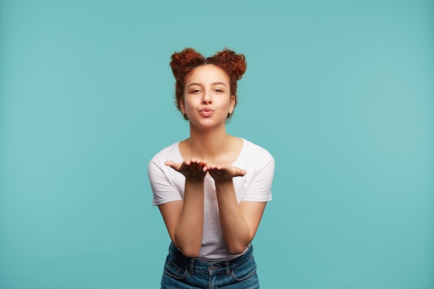 Positive young pretty curly brunette woman with bun hairstyle