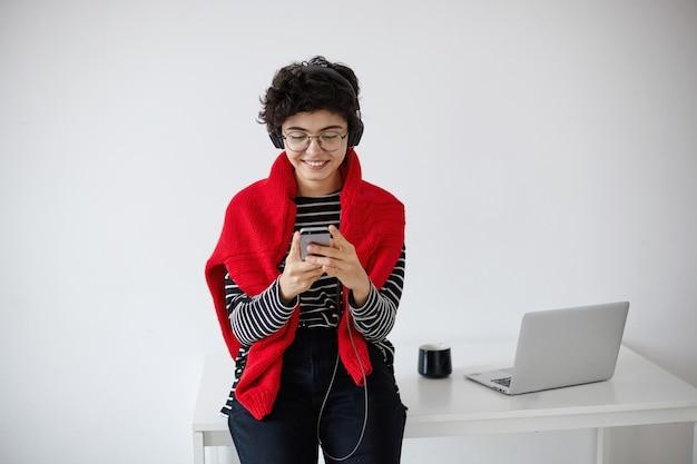 Positivo giovane donna bruna riccia abbastanza alla moda con taglio di capelli corto alla moda mantenendo il cellulare in mani alzate e guardando allegramente sullo schermo, isolato su sfondo bianco