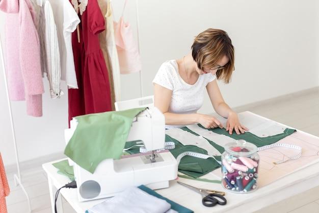 Позитивная молодая красивая девушка-швея-дизайнер работает над новым проектом, сидя за своим столом со швейной машиной в своей мастерской. творческая бизнес-концепция.