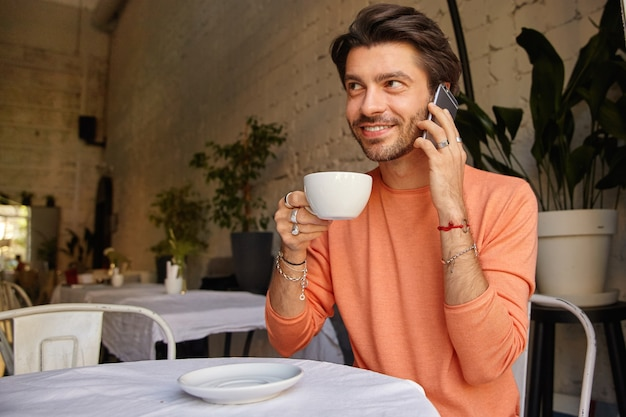 Positivo giovane maschio grazioso in maglione seduto nella caffetteria con una tazza di tè, guardando avanti e sorridendo felicemente, avendo una piacevole conversazione sul telefono cellulare