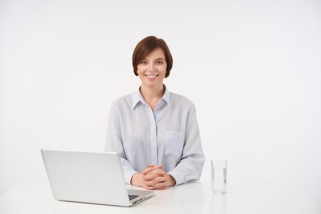 Позитивная молодая довольно короткошерстная брюнетка сидит за столом и складывает руки на столешнице, весело смотрит с очаровательной улыбкой, изолированная на белом