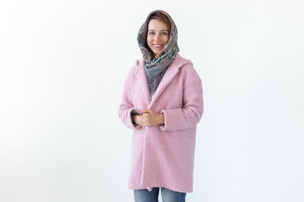스카프와 흰 벽에 분홍색 코트에 포즈 긍정적 인 젊은 예쁜 여자. 가을 봄 옷의 개념입니다.
