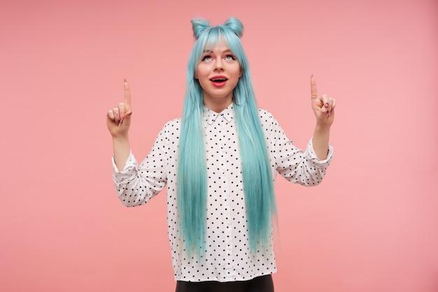 明るい化粧とエレガントな服を着て立っている間、上げられた人差し指で上向きに表示される長い青いアニメの髪を持つポジティブな若いきれいな女性