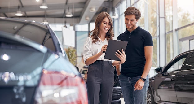 Positive young professional saleswoman demonstrating document to male customer buying new car in dealership