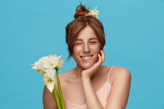 Positive young redhead attractive lady with bun hairstyle biting underlip while looking gladly at camera, holding bunch of white flowers while posing over blue background