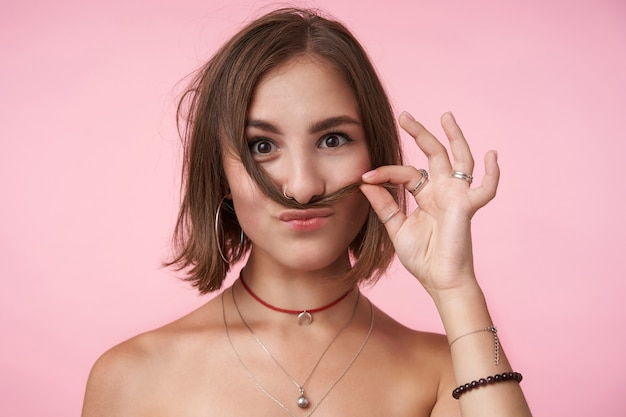 Positive young short haired brunette woman with natural makeup imitating mustache with her hair while making fun, being in nice mood while standing over pink wall