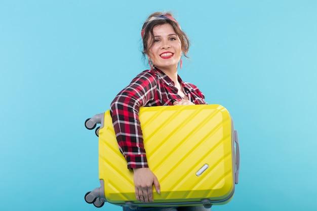 파란색 벽에 포즈 노란색 가방을 들고 격자 무늬 셔츠에 긍정적 인 젊은 웃는 여자. 관광 및 여행의 개념.