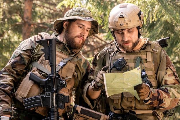 군복을 입은 긍정적인 젊은 군인들은 삼림 보호소에서 쉬면서 담배를 피우고 담소를 나눴다