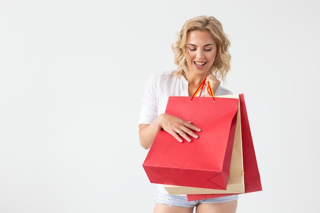 Positive young stylish blonde woman holding bags posing on a white background with copy space