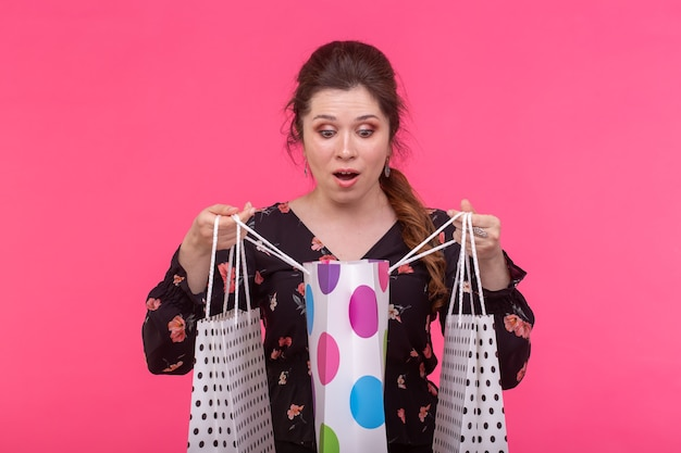 Positive young stylish woman holding bags posing on a pink background. shopping concept in a mall.