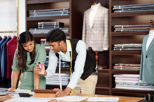 顧客のためのスーツに取り組んで、スケッチを描き、詳細を議論するインドの仕立て屋の前向きな若いチーム