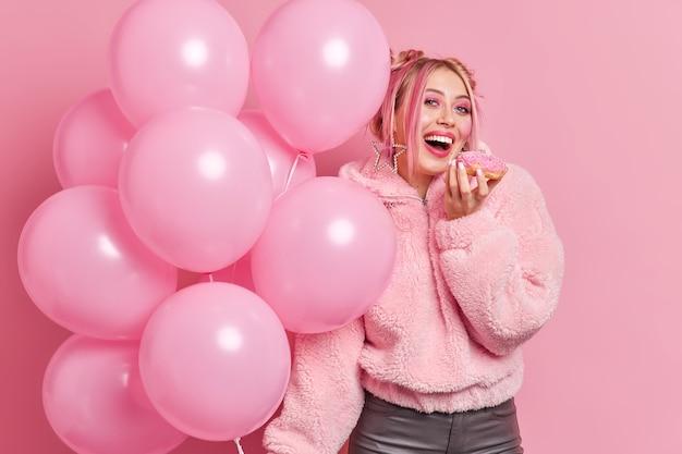 明るいピンクのメイクでポジティブな若い10代の少女は、おいしい甘いドーナツをかみます