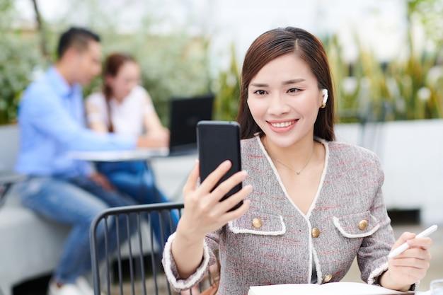 Позитивная молодая вьетнамская бизнес-леди сидит за столом в летнем кафе и разговаривает по видеосвязи с коллегой