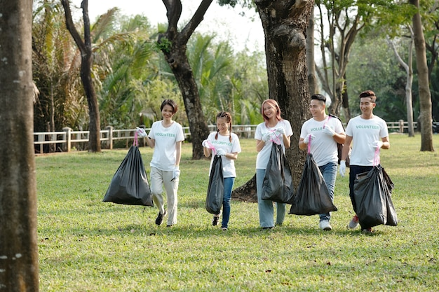 Positive young volunteers carrying bags of trash they picked on campus or in city park