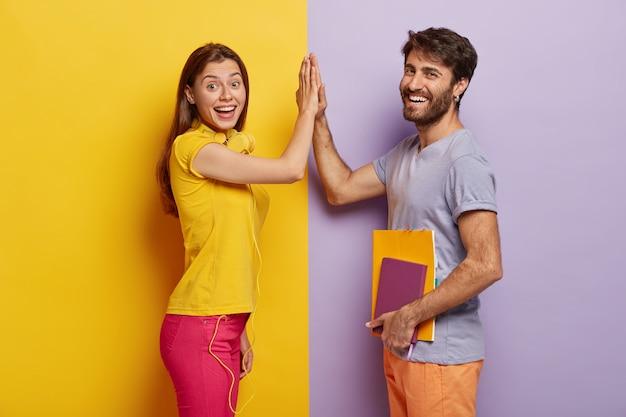 긍정적 인 젊은 여성과 남성이 하이 파이브를하고 팀으로서의 일에 동의하며 옆으로 서십시오