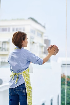Positive young woman in apron cleaning big window in apartment, view from the back