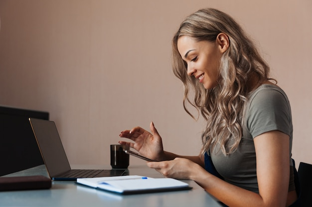 Позитивная молодая женщина на рабочем месте держит в руках мобильный телефон Premium Фотографии