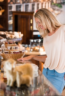 Positive young woman at the bakery store
