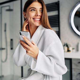 Positive young woman in a bathrobe
