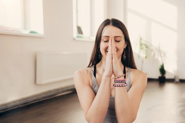 Положительная молодая женщина делая жест рукой namaste на студии