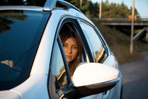 Позитивная молодая женщина за рулем автомобиля.