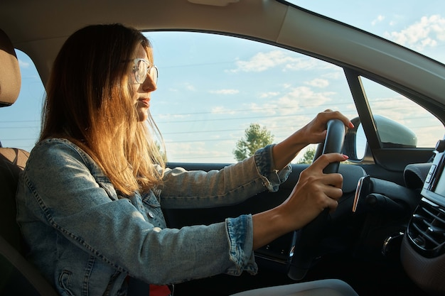 Positive young woman driving a car.