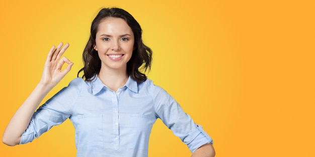 Positive young woman expressing happiness and showing ok