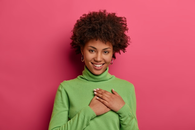 Positive young woman feels thankful, keeps hands pressed to heart, wears green turtleneck, smiles positively, looks with tender smile, isolated over pink bright wall. thank you very much