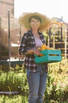 ポジティブな若い女性の庭師は、彼女の会社で収穫の間、彼女の手にレモンの箱を持っています。有機園芸の概念