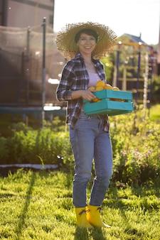 ポジティブな若い女性の庭師は、彼女の会社で収穫中にレモンの箱を手に持っています
