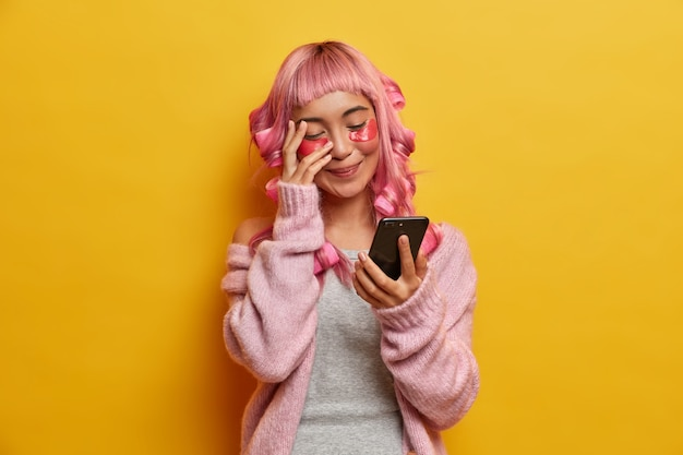 Positive young woman giggles positively and looks at smartphone display, reads funny news, has long pink hair, makes hairstyle, cares about skin