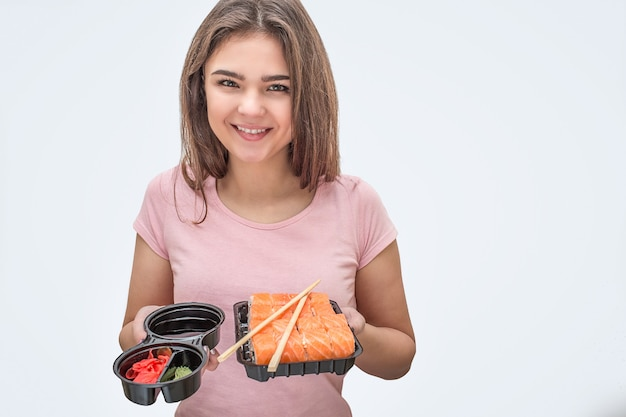 ポジティブな若い女性は、手に生姜と寿司と醤油を保持します。