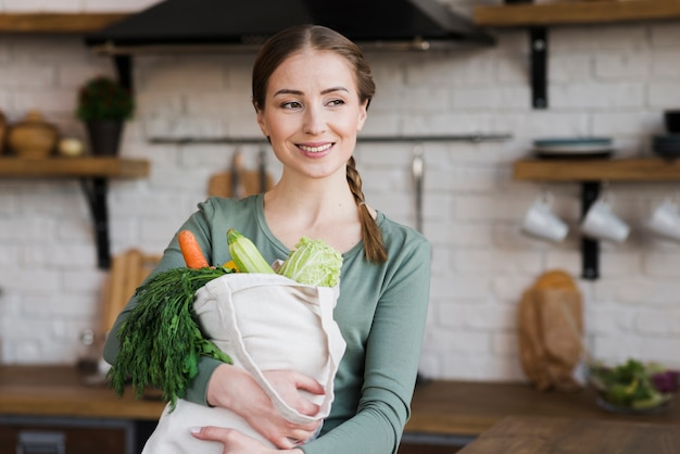Positive young woman holding bag with organic vegetables