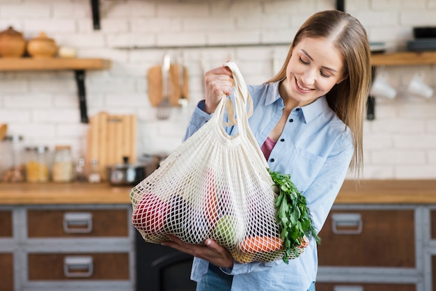 Positive young woman holding bags with organic vegetables