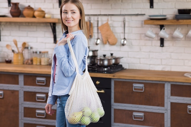 Positive young woman holding eco bag with organic fruits