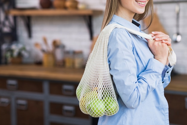 Positive young woman holding reusable bag with fruits